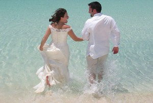 Bride & groom laughing and walking in the water on a beach