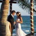 A bride and groom on a beach.